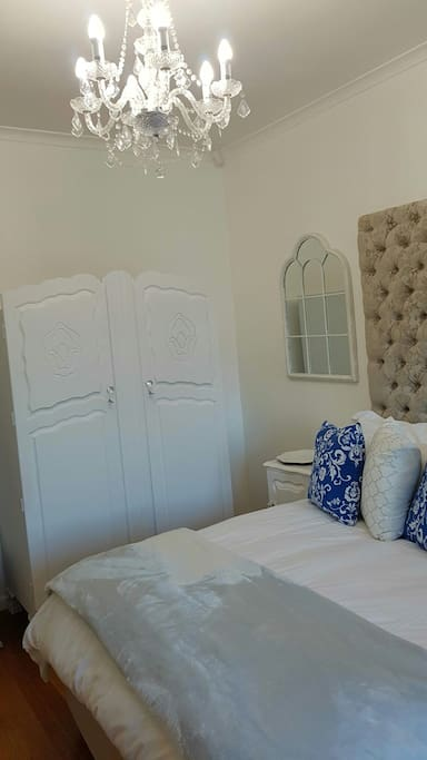 Bedroom 1 has a queen-sized bed, with lovely deep buttoned headboard,   aircondioning, TV with all DSTV channels and a separate bathroom across the hall with a Victorian bath, large shower, basin and toilet.