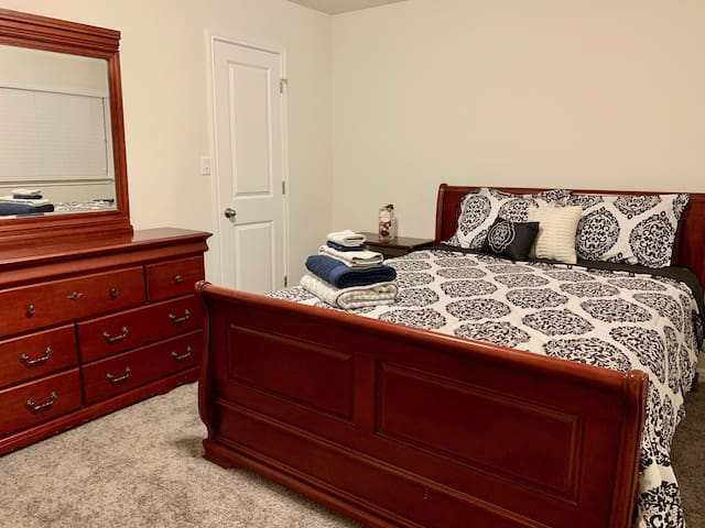 Moroccan Bedroom with comfy queen size bed, night stand, and dresser with mirror. Large walk-in closet.