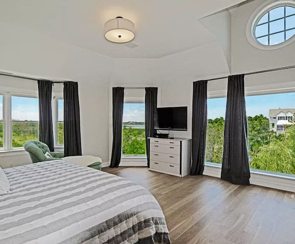 Master bedroom with double-height ceilings and sunset views