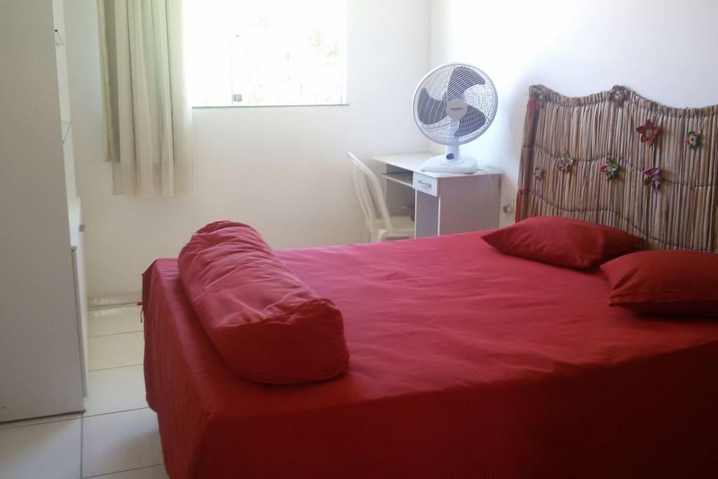 Quarto com cama de casal, ar condicionado, estantes e ventilador.