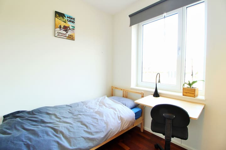 The 2nd bedroom on the first floor has a cozy single bed and also offers you a work space.