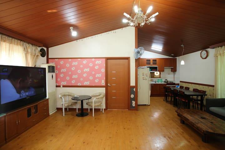 넓은 거실과 골드톤의 침실, 테라스가 있는 분리형 단체 객실