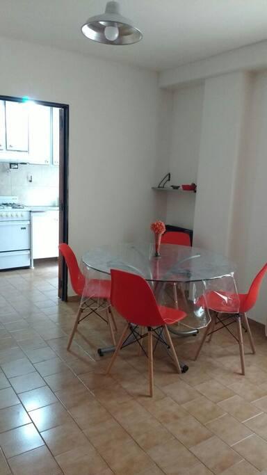 Living- comedor, mesa redonda con 4 sillas, vista hacia la cocina.
