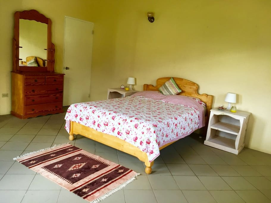 Large bedroom with queen size bed with four windows to let the sea breeze in