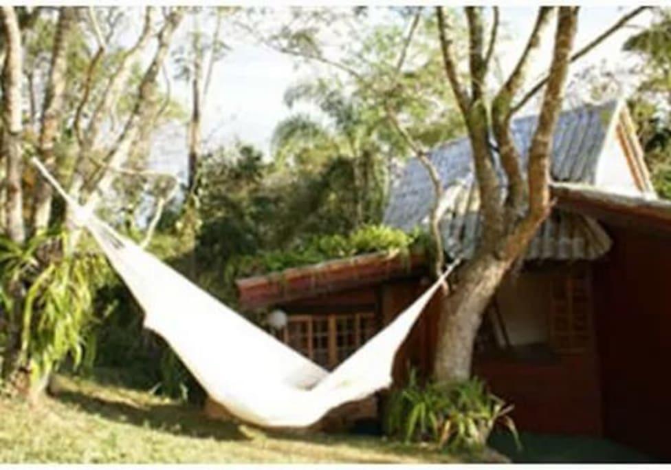 Espaço externo com churrasqueira e rede de descanso.
