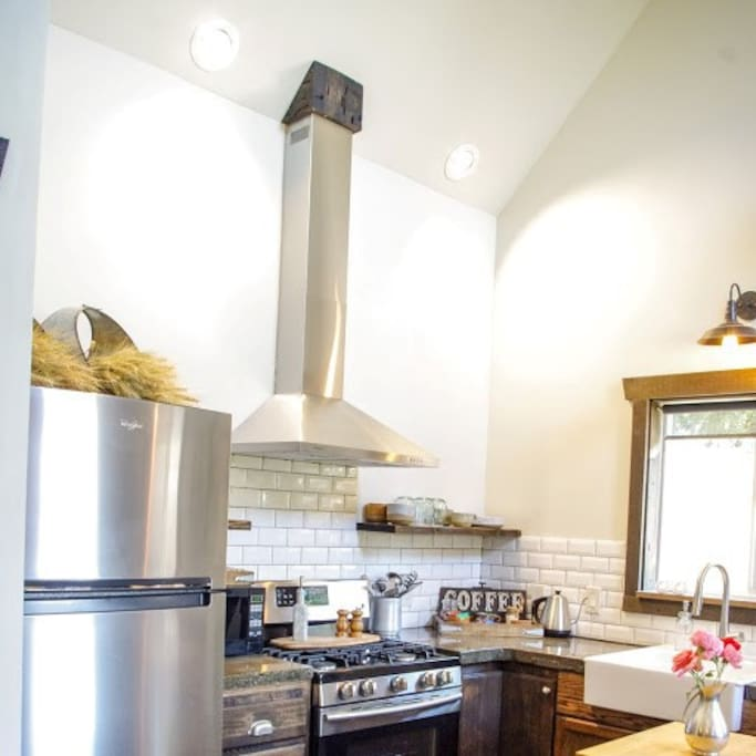 A cozy kitchen with a full size stove and refrigerator,