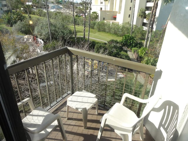 Balcony with seating & views of Universal Orlando theme parks & community pool.