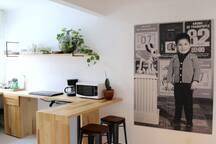Cocina con cafetera, licuadora, estufa eléctrica y horno de microondas.