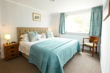 Comfortable king-size bedroom with views looking across the surrounding countryside.