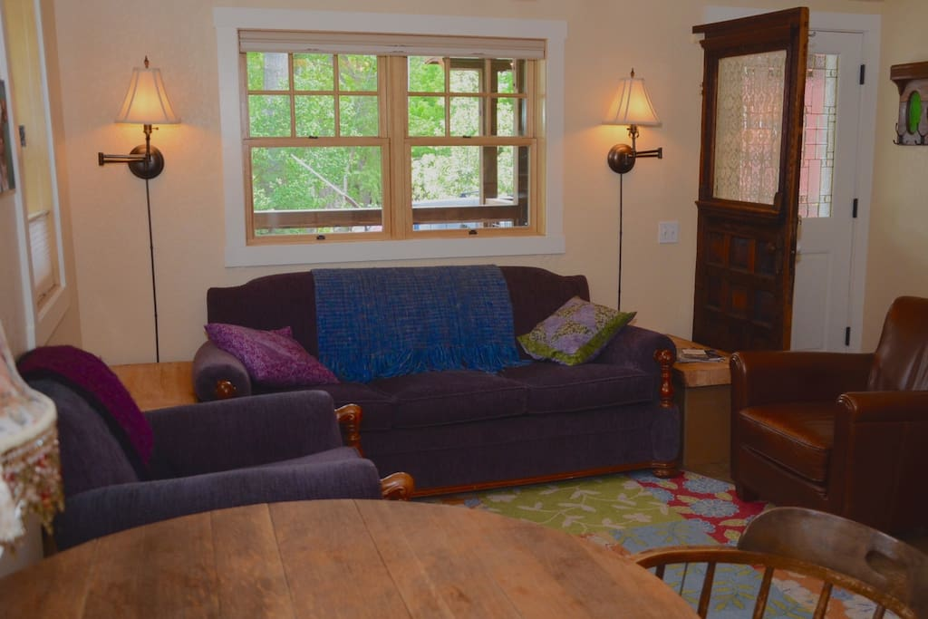 Have a seat in the charming living area featuring a 1940's refurbished couch and chairs in purple of course!