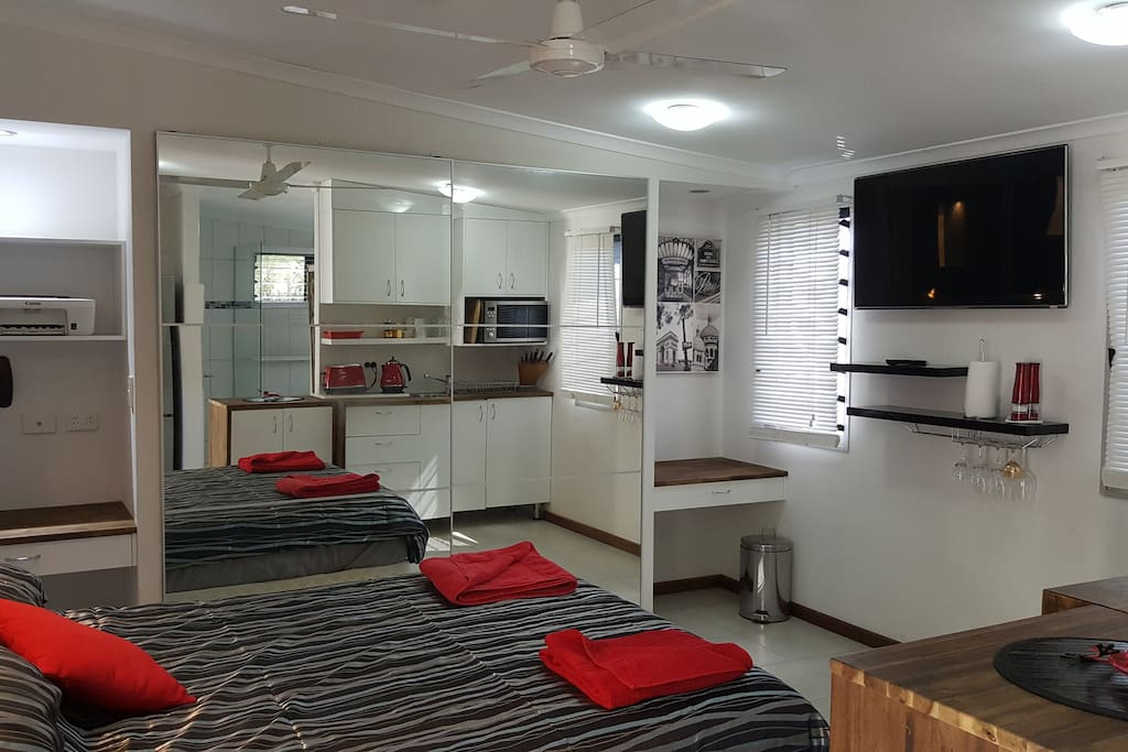 Wall mounted TV, big wardrobe with full-length mirrors, and desks