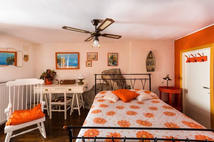 """la """"stanza della roccia"""", camera da letto 4 al primo piano. La stanza non dispone di aria condizionata, è in genere più fresca delle altre perché non esposta al sole. Ha una porta finestra che si affaccia sull'ingresso principale."""
