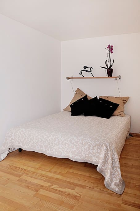 Double bed, situated behind a light wall