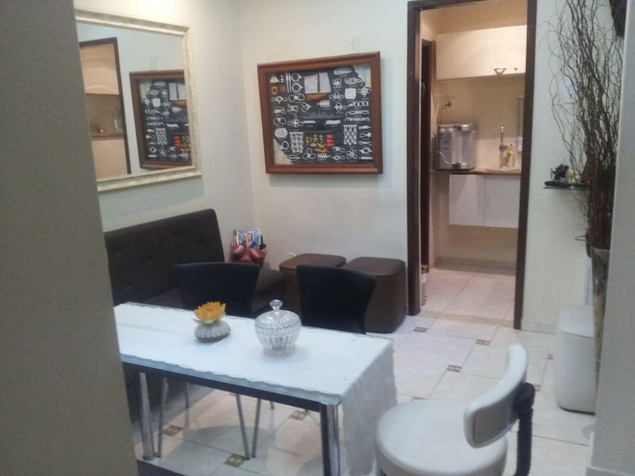 Sala ampla com televisão digital; cozinha com frigobar, filtro, cafeteira e micro-ondas.