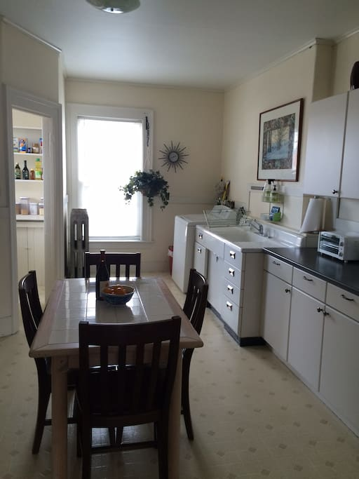 Bright, sunny kitchen, with laundry machines included. Pantry is to the left.