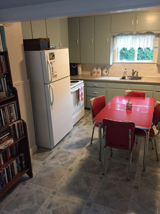 The kitchen is true to the day it was built with the original cupboards and a vintage red Formica table.