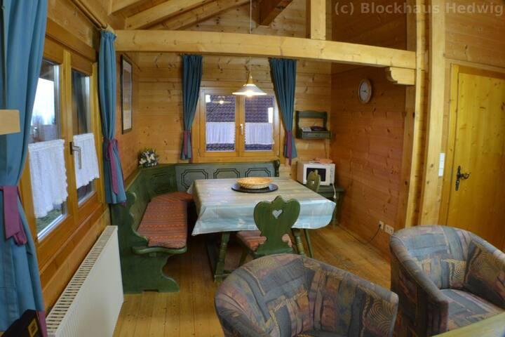 Essbereich im Wohnzimmer mit grossem Tisch, Ecksitzbank und Mikrowelle