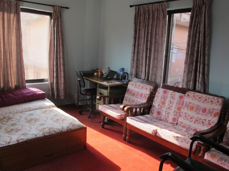 Spacious room, with twin bed, table and chair, and Nepali designed sofa