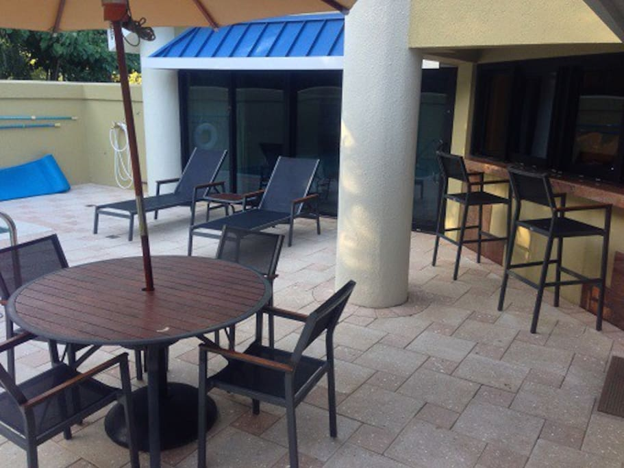Patio furnished with an umbrella-canopied table with 4 chairs  & 2 lounge chairs. A shaded bar with stools is on the patio just outside the kitchen. Opening the kitchen windows allows meals to be placed directly onto the patio bar.