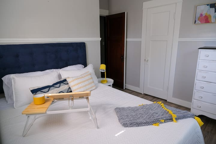 Bedroom 1 features a bold headboard and a lap desk, a funky throw pillow and cozy blanket, a lamp with USB ports for charging your devices, and a large dresser.