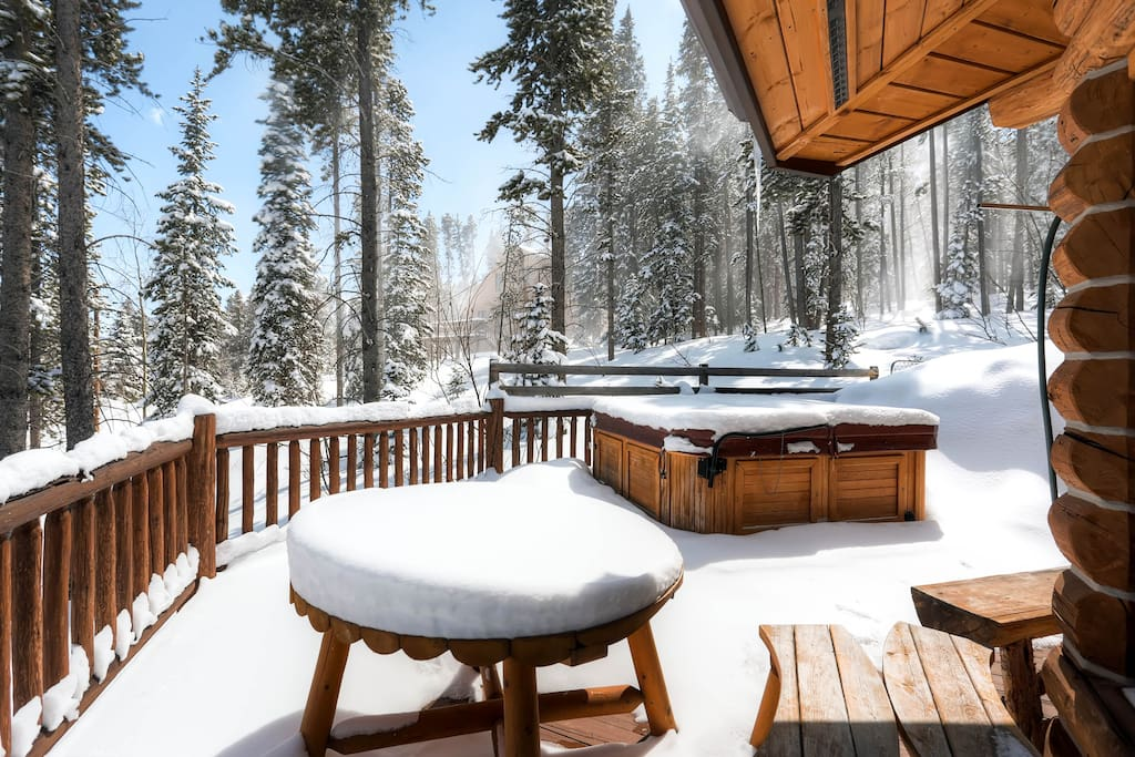 Enjoy the serenity of the surrounding woods on the back deck with the modern comforts of this hot tub and outdoor dining table.