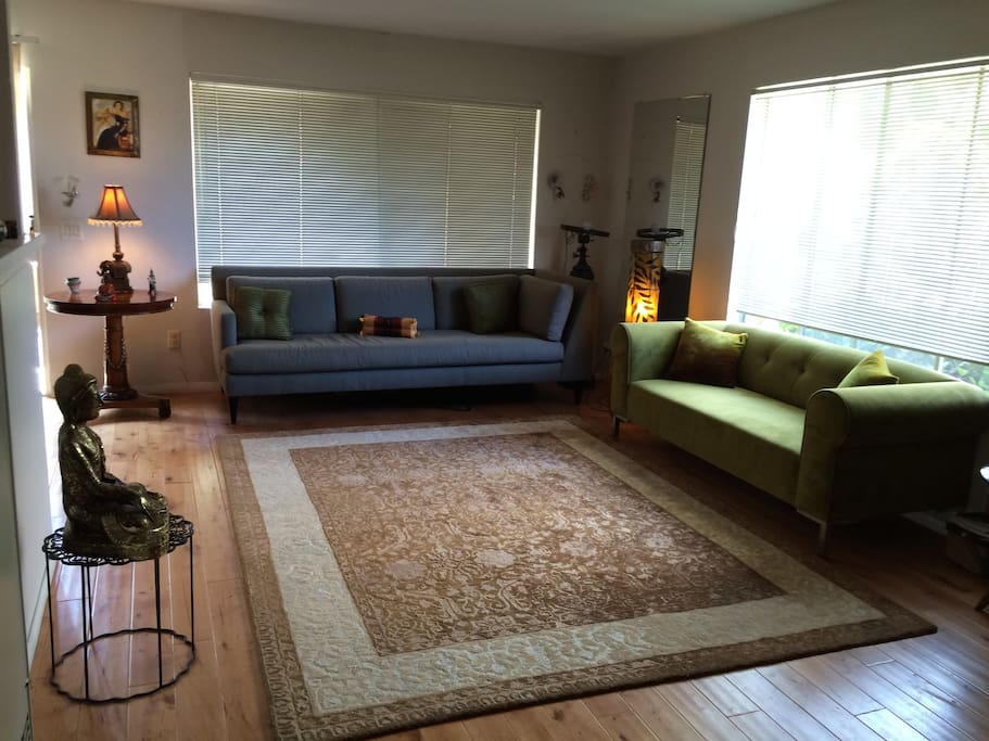 Spacious living room with area rug and comfortable couches. Cross breeze and lots of natural light.