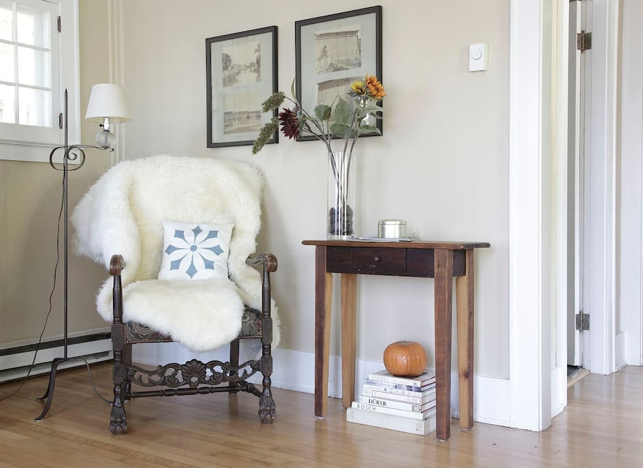 reading nock with antique lamp and english arm chair, side table and sheep skin throw