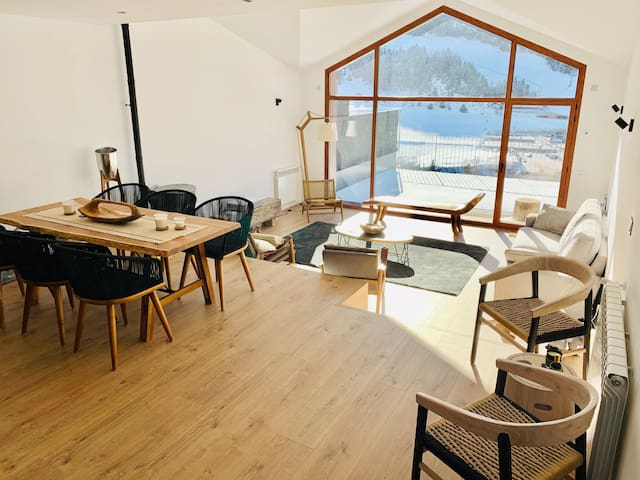 2-level living and dining room with a fireplace and custom made furniture from Bali, Indonesia.  Our modern 3 bedroom chalet in  El Tarter  offers amazing panoramic views over the ski slopes of Grandvalira.  Kabano Vacation Rentals Andorra