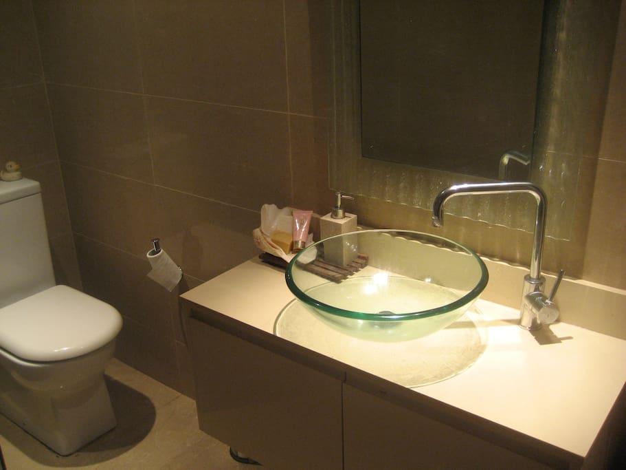 Modern bathroom, large rain shower head move-able, floor to ceiling limestone tiles