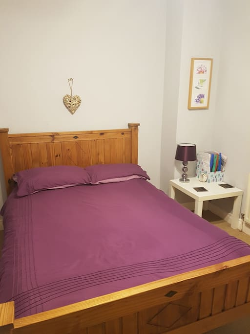 Double bed. Wooden rail for clothes also provided in room.