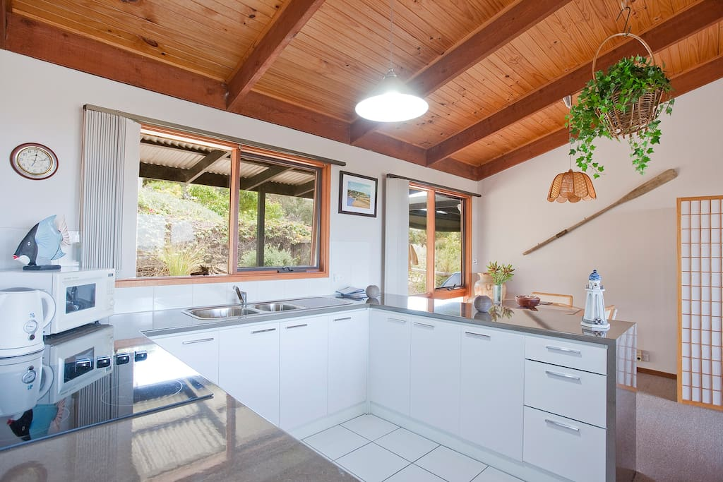 Bright, airy fully equipped kitchen to cook up a storm, with dining area in background.