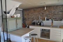 La cuisine est toute équipée : four, plaques à induction, micro-ondes, lave vaisselles...