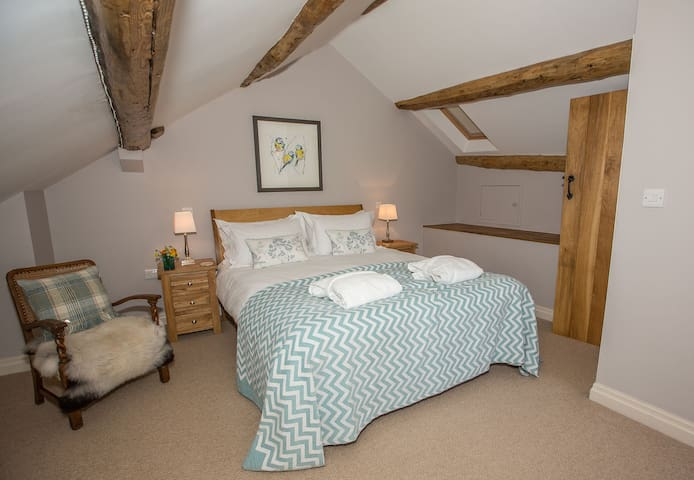 King size bed & exposed beams in bedroom