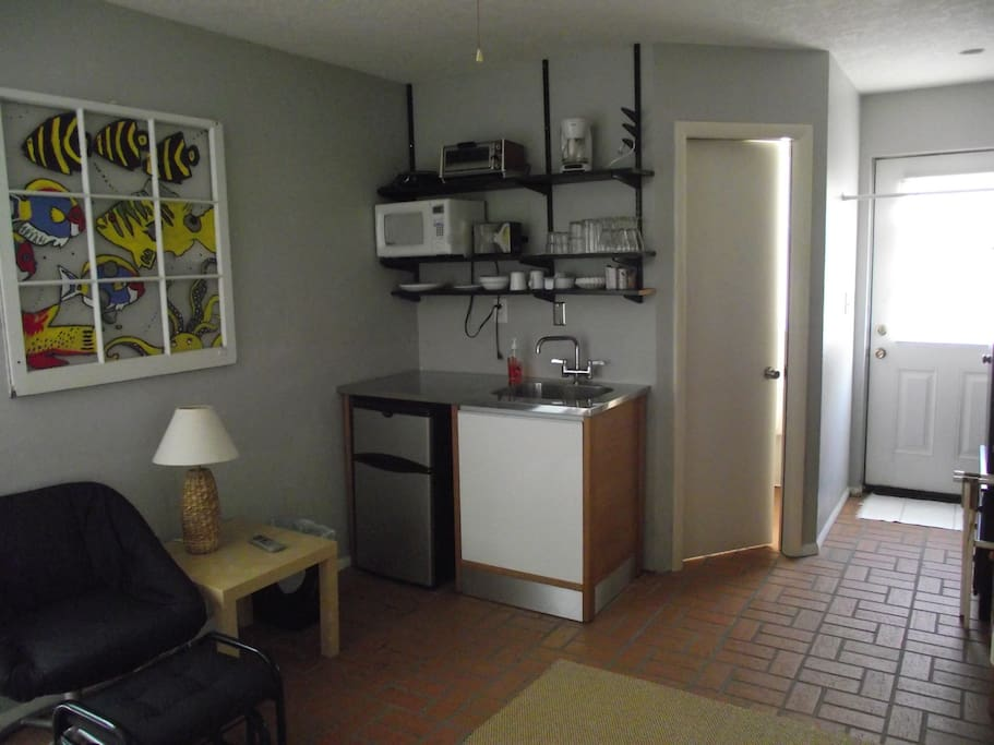 From an angle in the room looking at Kitchen area and bathroom door
