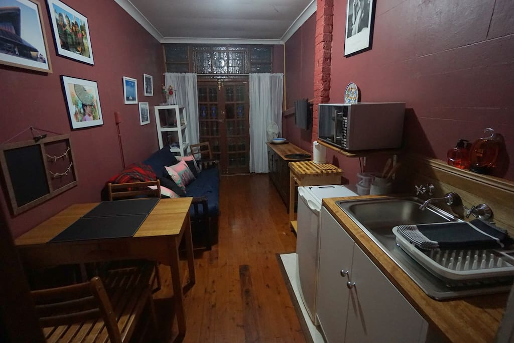 Living space includes kitchenette with sink, fridge and microwave.