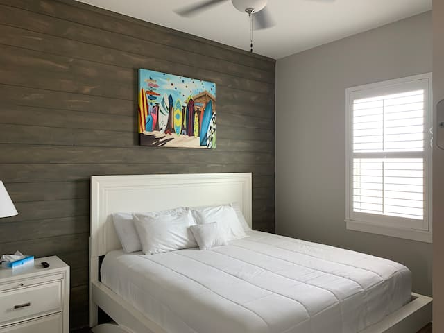 """Bedroom #2 has a comfortable kind sized bed, it's own 50"""" tv. This bedroom is located in the third floor."""