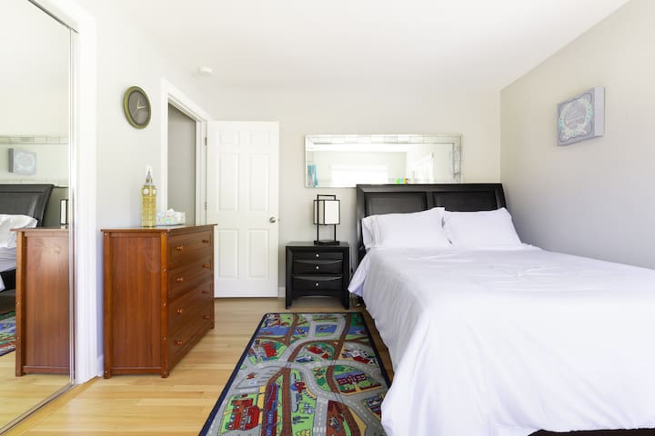 Bedroom #3 has a Queen-sized bed and gets flooded with natural light from the two large bedroom windows