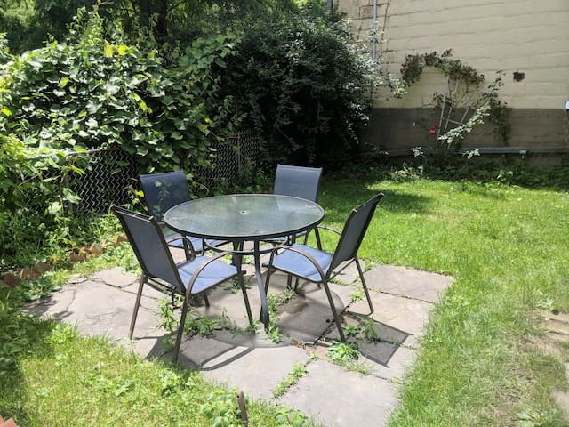 Table and chairs in the small fenced in back yard (shared area for all guests)