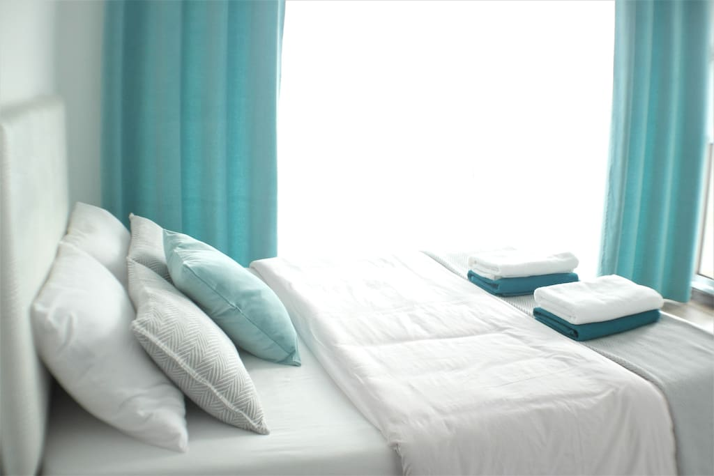 Master bedroom double bed with fresh bed linen and towels
