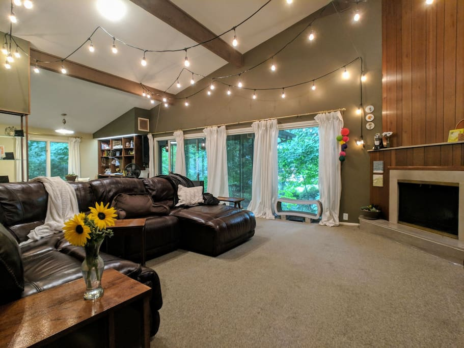 Living room with  windows facing the ravine, draped lights above, and a comfy couch for watching tv.
