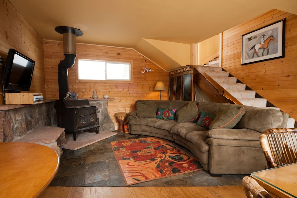 Living room area/ original wood stove/ large screen t.v. with Hulu and Netlfix/ 100 popular D.V.D.s and Videos
