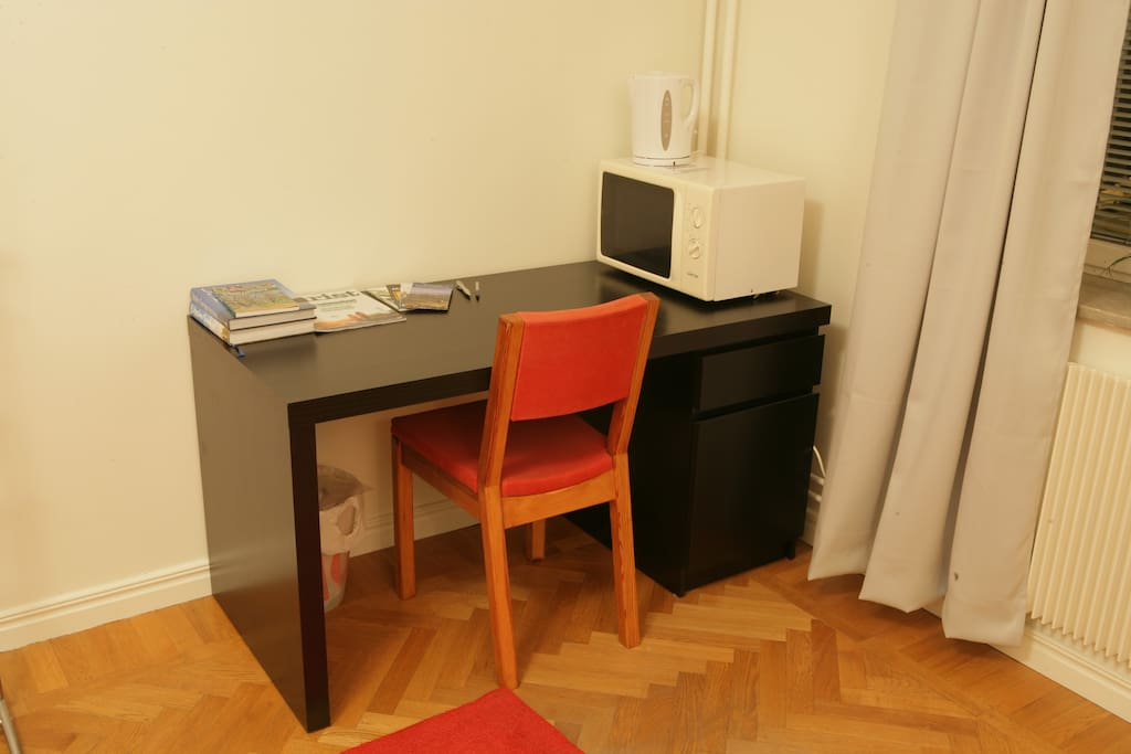 A small workspace, microwave and electric kettle, and a few guidebooks to Sweden.