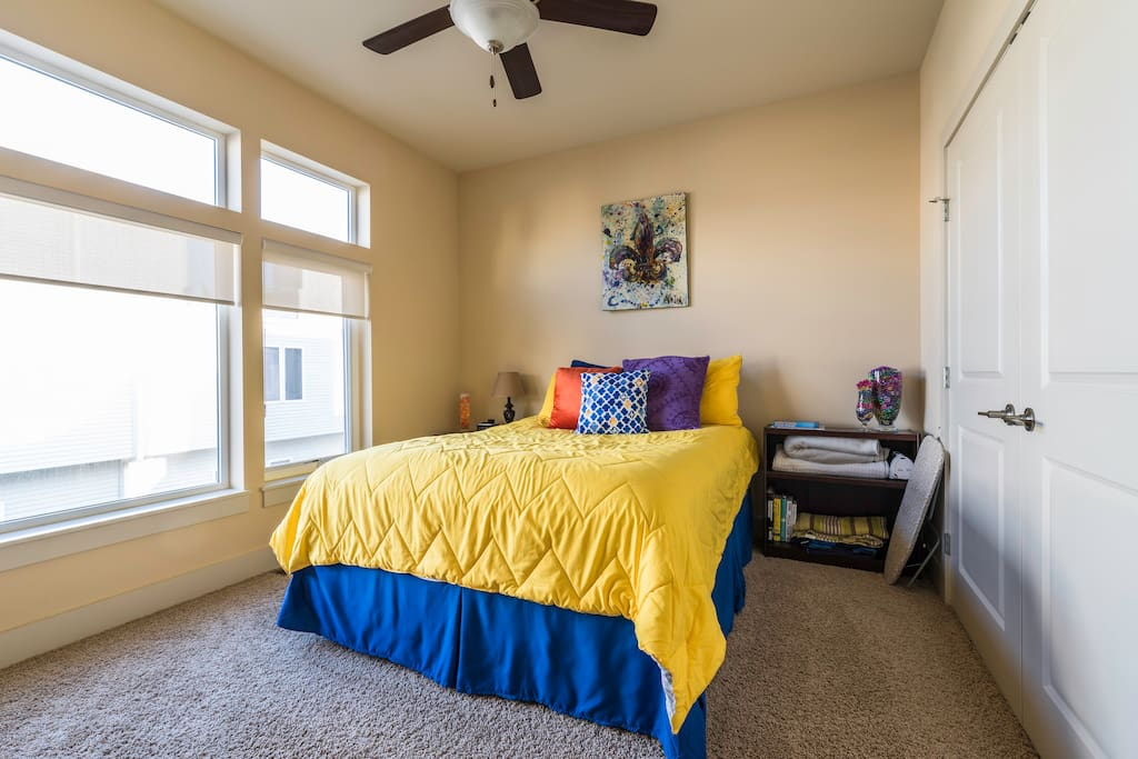Your room with large windows with plenty of light, space in closet to hang clothes, iron and ironing board in room as well.