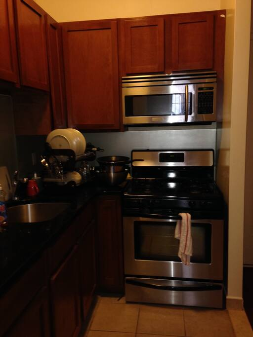 Kitchen with stainless steel appliances and fully stocked dining sets, wine glasses etc