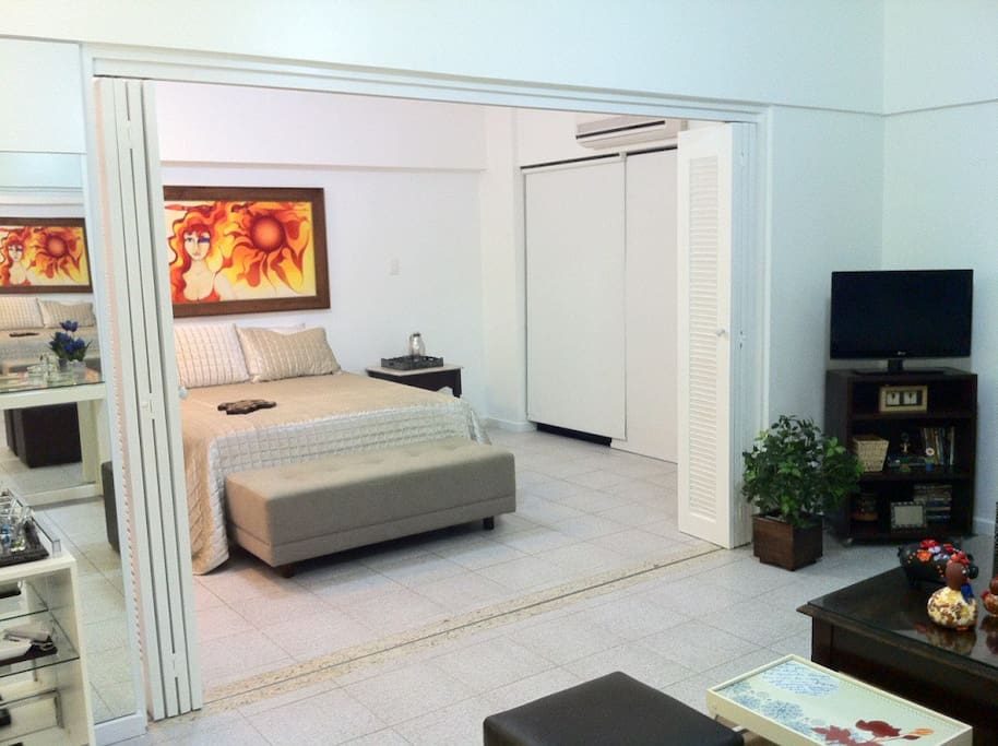 62m2 apartment divided into bedroom and living room separated by a sliding door. Both the lounge and the bedroom have ceiling fans and air conditioners.