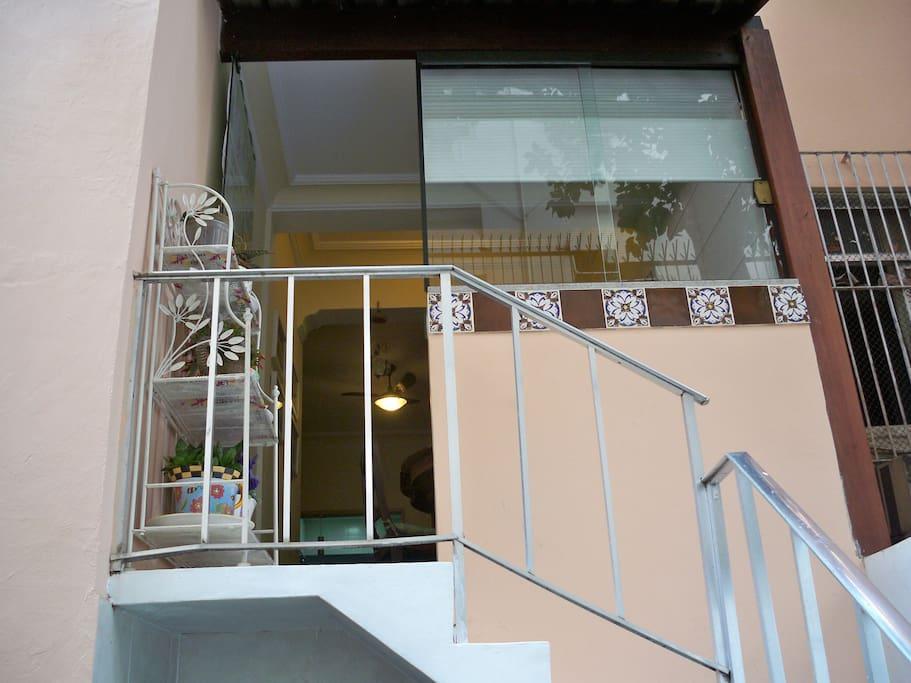 Porta de vidro que permite acesso ao pequeno jardim