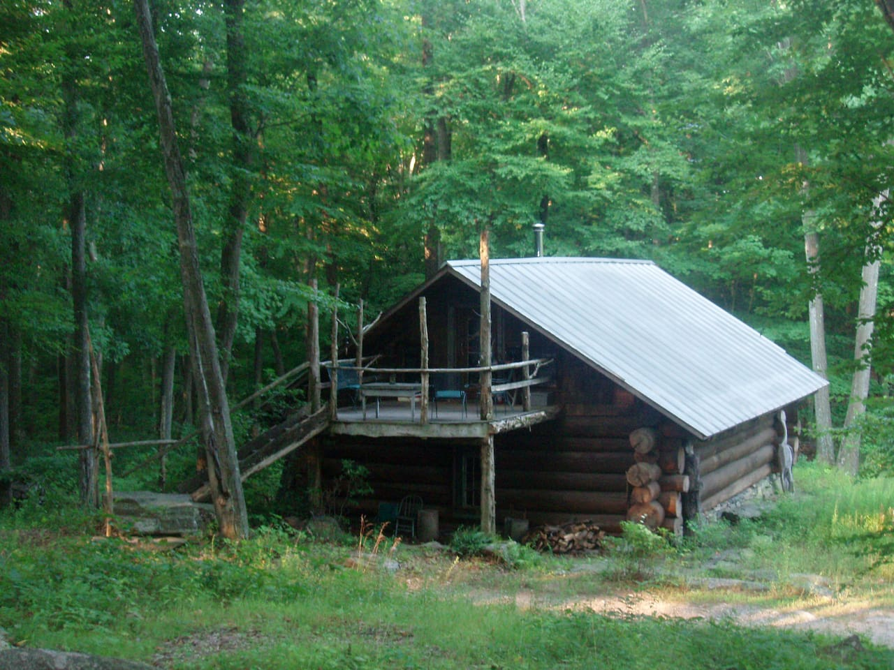 Hand Hewn Tulip Tree Log Cabin with Deck overlooking Pond.