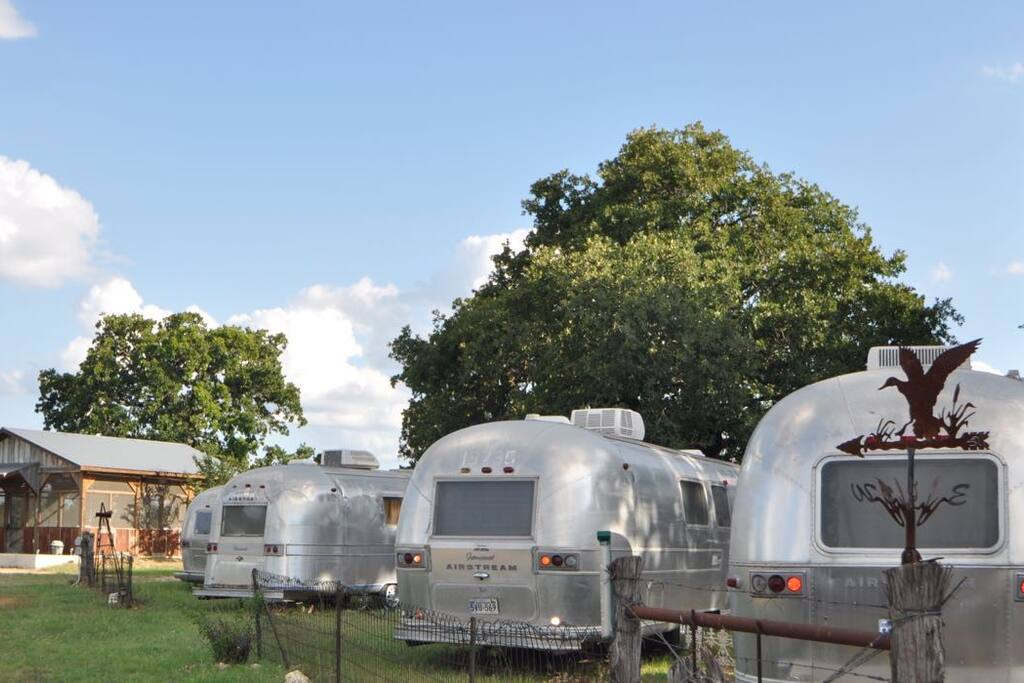 4 of the 6 airstreams and sleeping porch nestled among our giant oak trees