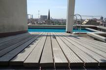 sun bathing deck next to pool with view of the Sea