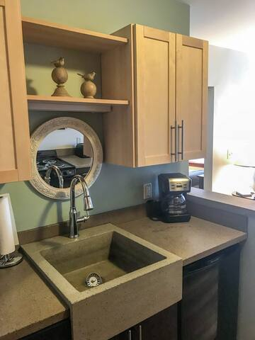 The kitchen includes a stove, oven, microwave, coffee maker, toaster, and dishes.